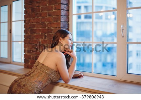 Portrait of Beautiful Stylish Woman Looking in Window. Day Light. Selective Focus.