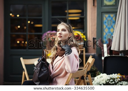 Portrait of beautiful stylish young woman sitting in street cafe . Model looking aside. City lifestyle. Female fashion.  - stock photo