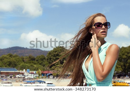 Portrait of beautiful tanned woman on pier with hair waving by wind in black sunglasses and stylish elegant clothes poses enjoying amazing view. Fashion look. Phuket island, Thailand - stock photo