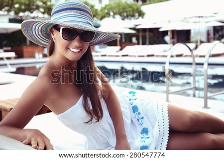 Portrait of beautiful tanned woman, relaxing beside a luxury swimming pool. Girl at travel spa resort pool. Summer luxury vacation. (focus on woman face) - stock photo