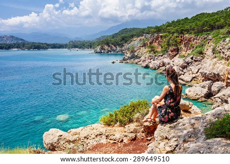Portrait of beautiful tanned woman sitting at the sea coast. Hot summer day and bright sunny light. Panoramic view on sea shore near Kemer, Antalya, Turkey. - stock photo