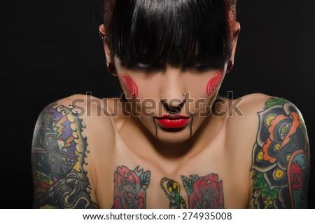 portrait of beautiful tattooed women on dark background - stock photo