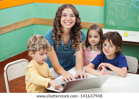 Portrait of beautiful teacher and students with laptop in classroom - stock photo