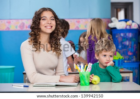 Portrait of beautiful teacher with bored boy sitting at desk in classroom - stock photo