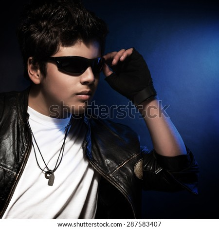 Portrait of beautiful teen boy wearing stylish sunglasses and leather jacket over blue background, fashion accessories for teenager