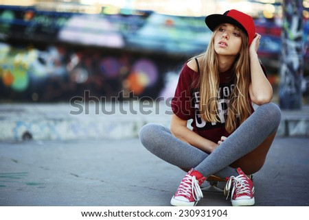 Portrait of beautiful teen girl sitting on skateboard over wall with abstract graffiti art. Urban outdoors, teenager's lifestyle - stock photo