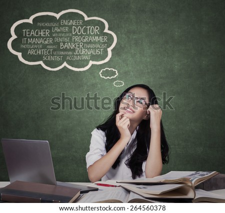 Portrait of beautiful teenage girl sitting in the class while dreaming her future goals - stock photo