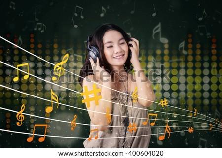 Portrait of beautiful teenage girl using earphones to listen music - stock photo