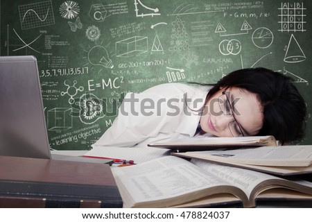 Portrait of beautiful teenage schoolgirl sleeping on desk over textbooks and looks tired after studying