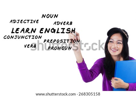 Portrait of beautiful teenage student studying foreign language and write english material - stock photo