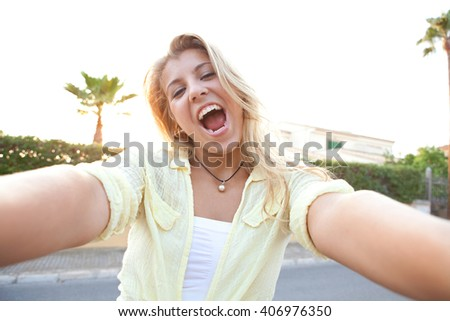 Portrait of beautiful teenager girl holding a smart phone to network, taking selfies photos and videos in home exterior sunset, outdoors. Technology lifestyle, expressive adolescent looking at camera. - stock photo