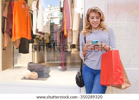 Portrait of beautiful teenager young woman in city shopping street by fashion store window, smiling using a smartphone, networking outdoors. Adolescent consumer using technology, lifestyle exterior.