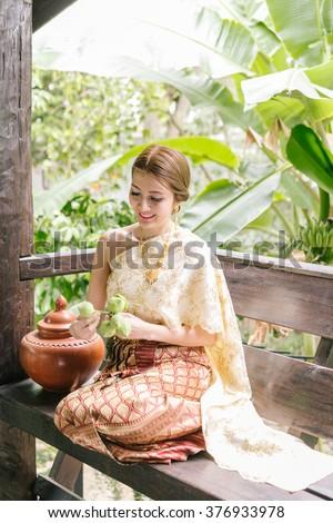 Portrait of beautiful Thai woman in Thai traditional costume,thai dress,Thai women wearing typical Thai dress, identity culture of Thailand - stock photo