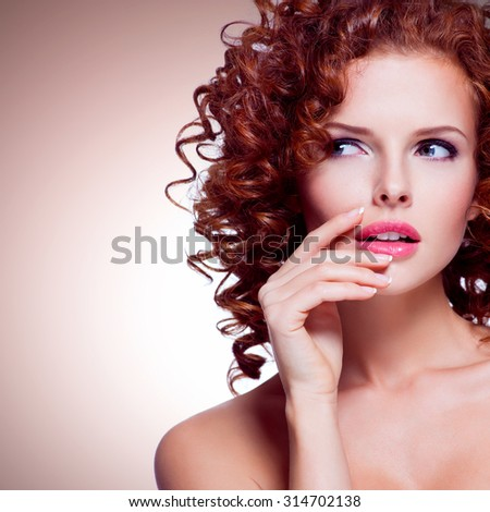 Portrait of beautiful thoughtful woman with curly hair posing at studio over beige background. - stock photo