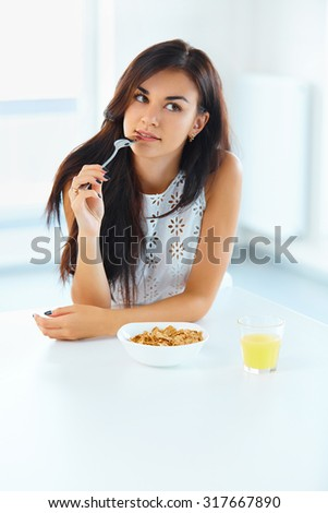 Portrait of beautiful thoughtful young woman eating cereals. Healthy eating. Health care. Wellness concept. Dieting concept. - stock photo