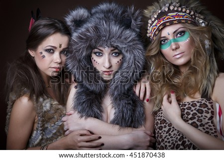Portrait of beautiful three young girls of America in the fur and Indian outfit - stock photo