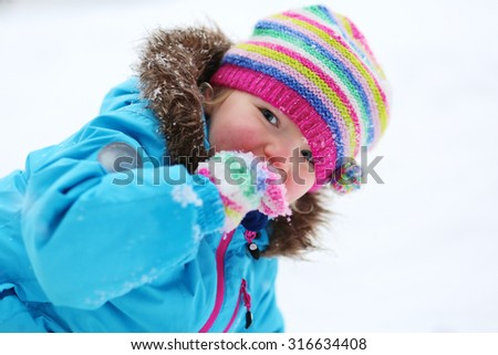 Portrait of beautiful toddler girl playing outdoors with snow. Happy little child wearing colorful knitted hat and blue coat enjoying winter day int he park.