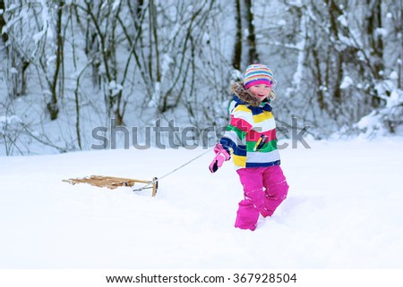 Portrait of beautiful toddler girl playing outdoors with snow. Happy little child wearing colorful knitted hat and blue coat enjoying winter day in the park or forest. - stock photo