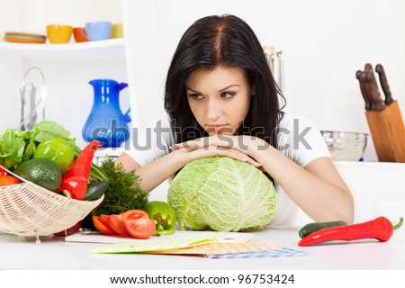 portrait of beautiful unhappy woman in the kitchen, sad lying on cabbage, sitting at the table - stock photo