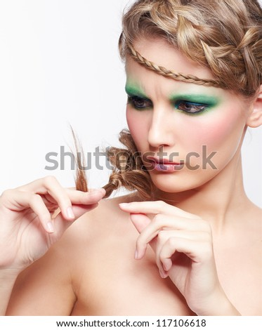 portrait of beautiful upset young dark blonde woman with creative braid hairdo looking at splitting ends