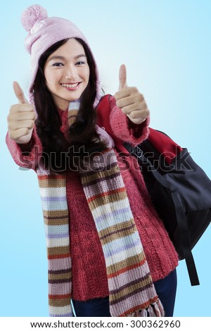 Portrait of beautiful wearing winter clothes while giving thumbs up and carrying backpack - stock photo