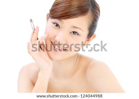 Portrait of beautiful woman applying lipstick using lip concealer brush