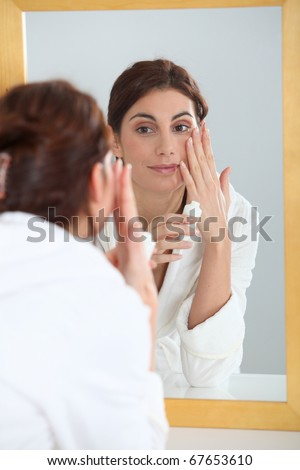 Portrait of beautiful woman applying moisturizer - stock photo