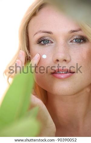 Portrait of beautiful woman applying moisturizer - stock photo