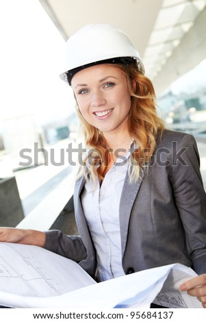Portrait of beautiful woman architect looking at plan