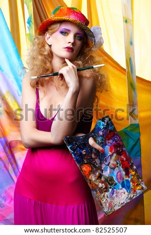 portrait of beautiful woman artist with paintbrush and palette standing in front of the easel with painted cloth on it - stock photo