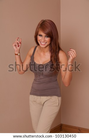 Portrait of beautiful woman at home laughing with her hands in the air - stock photo