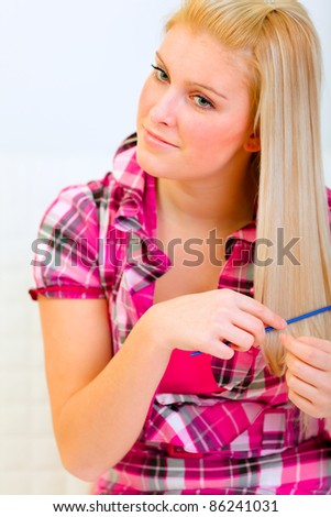 Portrait of beautiful woman combing hair