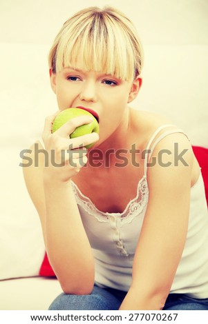 Portrait of beautiful woman eating an apple.
