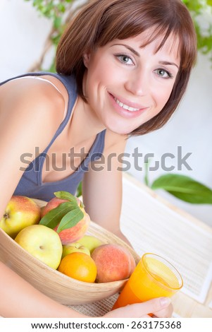 Portrait of beautiful woman eating fresh ripe fruits and drinking juice at home, loss weight, dieting and healthy nutrition concept - stock photo