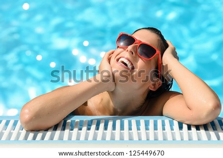 Portrait of beautiful woman face with red sunglasses in swimming pool. Pleasure moment in spa resort on hot summer day. Blue bokeh water background. - stock photo