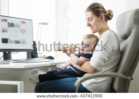 Portrait of beautiful woman feeding her baby from bottle while working at office - stock photo