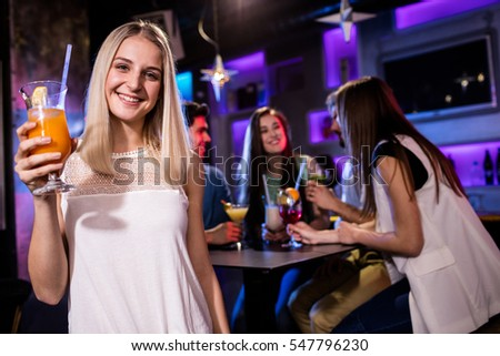 Portrait of beautiful woman having a cocktail in bar