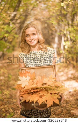 Portrait of beautiful woman hold in hands old retro vintage case with many autumn leaves Young adult girl stand in fall park , wear short sexy dress Alley in perspective Sunny day
