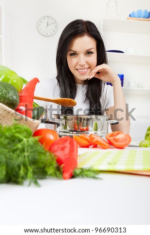 portrait of beautiful woman hold pan with ready meal, soup, boiler in the kitchen, happy smile - stock photo