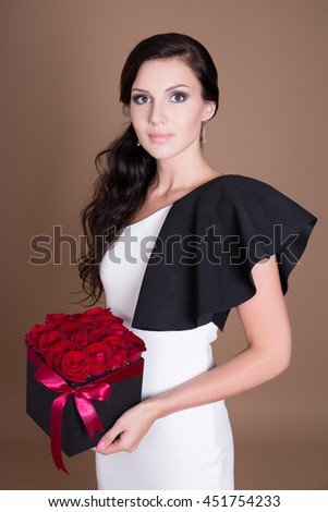 portrait of beautiful woman holding box with red rose flowers