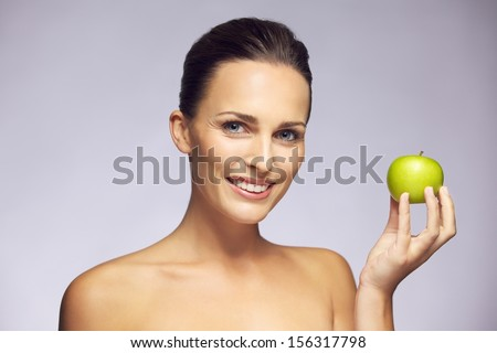 Portrait of beautiful woman holding green apple. Healthy looking young woman smiling against gray background.