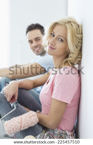 Portrait of beautiful woman holding paint roller with man in background - stock photo