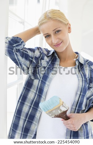 Portrait of beautiful woman holding paintbrush in new house - stock photo