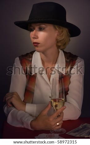 Portrait of beautiful woman in a black hat with a wine glass - stock photo