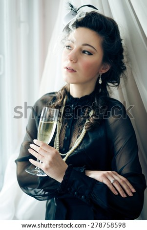 Portrait of beautiful woman in black dress and glass of champagne and looking out the window - stock photo
