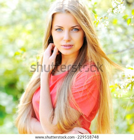 Portrait of beautiful woman in blooming tree in spring - stock photo