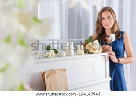 Portrait of beautiful woman in blue dress standing near the piano with white flowers