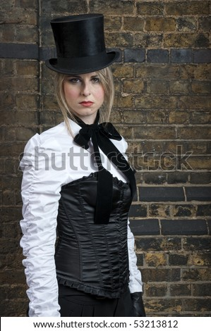 Portrait of beautiful woman in late victorian costume against brick wall