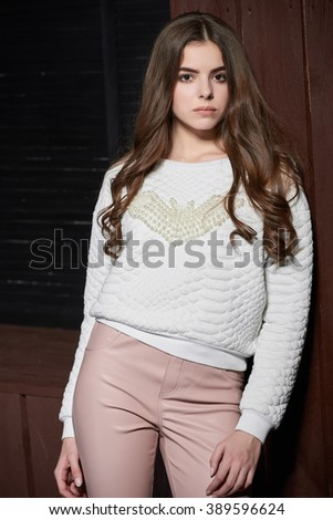 Portrait of beautiful woman in pink pants and white sweater - stock photo