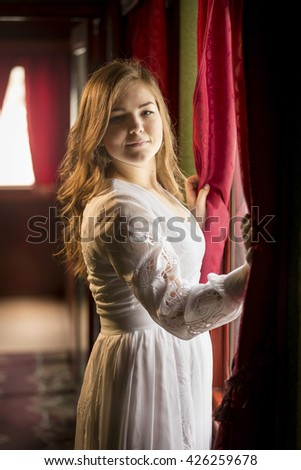 Portrait of beautiful woman in retro dress posing at big window in old house - stock photo